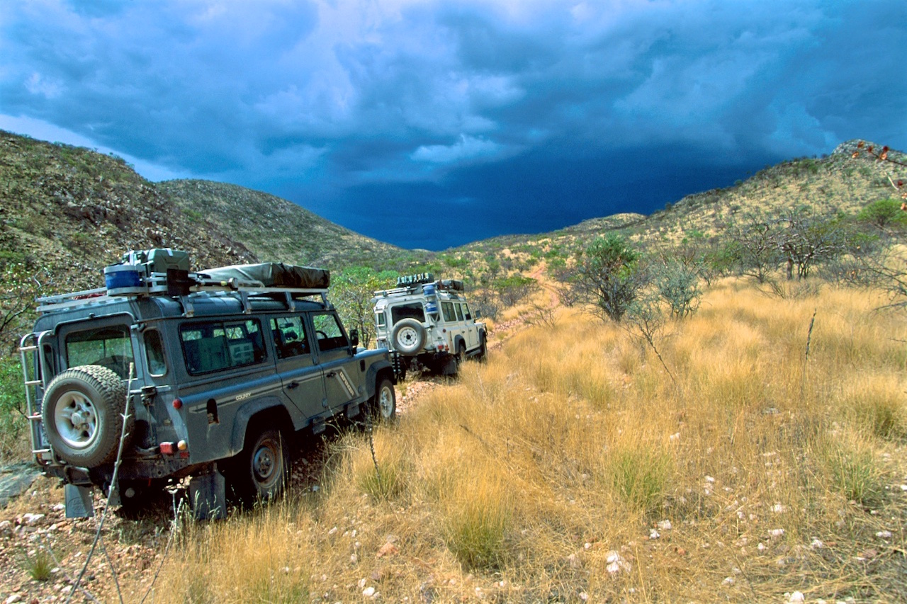 Defender 110s passing in front of storm