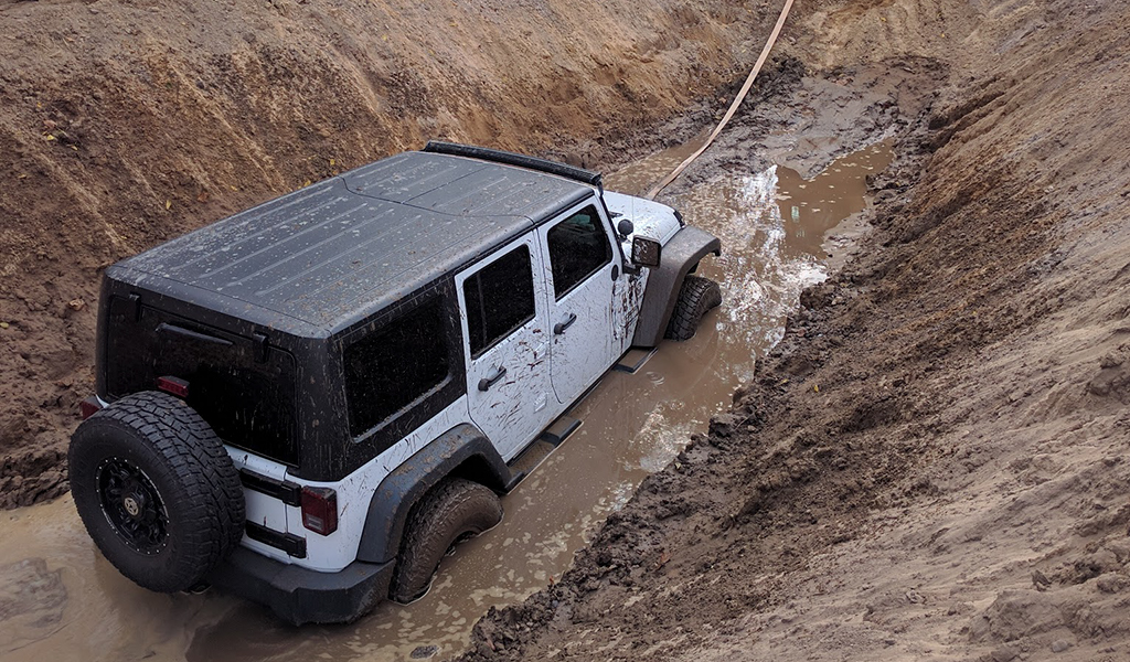 White Jeep in muddy hole
