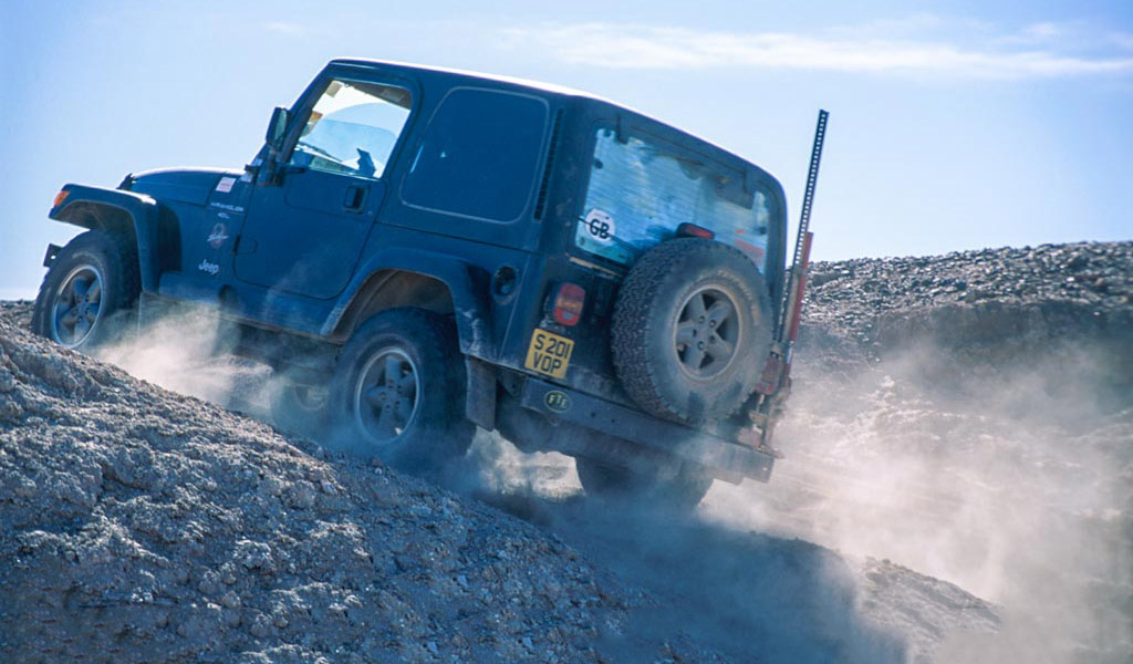 Jeep driving up rough track